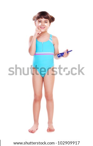 Girl in a swimsuit using a cream to protect face skin from the sunburn - stock photo