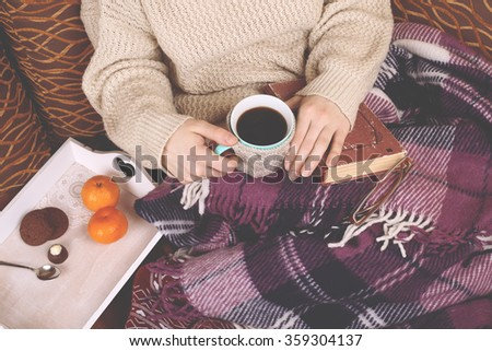 Girl in a warm winter beige sweater holding book, cup in a knitted cover, on lap tray with sweets and tangerines, the concept of comfort and relaxation - stock photo