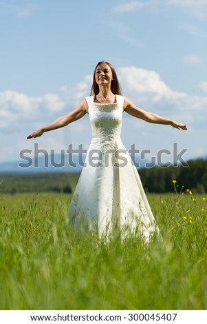Girl in a wedding dress in his arms flying field - stock photo