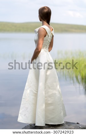 girl in a white dress standing on a rock against the backdrop of the lake, the view from the back - stock photo