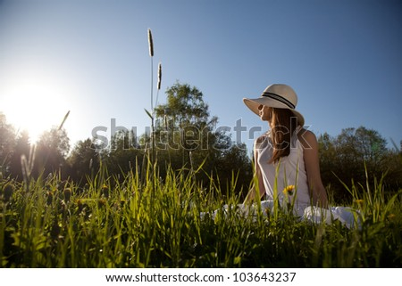 girl in a white hat sitting on the grass - stock photo