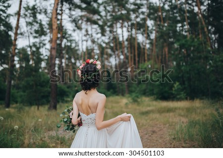girl in a white wedding dress with a bouquet of red flowers and greens in hands stands on a meadow in the woods - stock photo