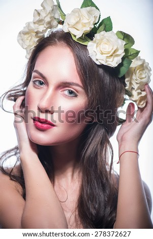 Girl in a wreath of beautiful flowers. beautiful brunette girl with red lips - stock photo