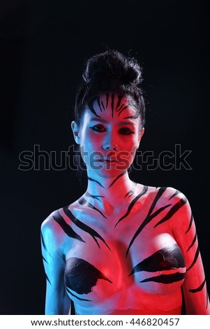 Girl in Airbrush Body Paint with Zebra skin art in Black background, low key studio lighting, red blue gel color - stock photo