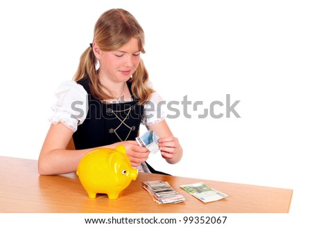 Girl in bavarian dirndl with yellow piggy bank - stock photo