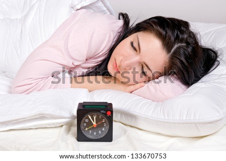 girl in bed with alarm clock - stock photo