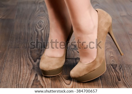 Girl in beige suede high-heeled shoes on the wooden floor - stock photo