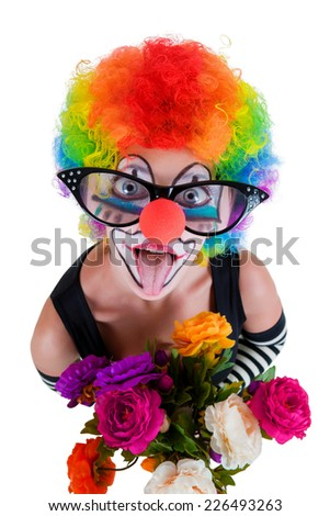 Girl in big red glasses and clown costume with a bouquet of flowers puts out the tongue looks up isolated on white background. - stock photo