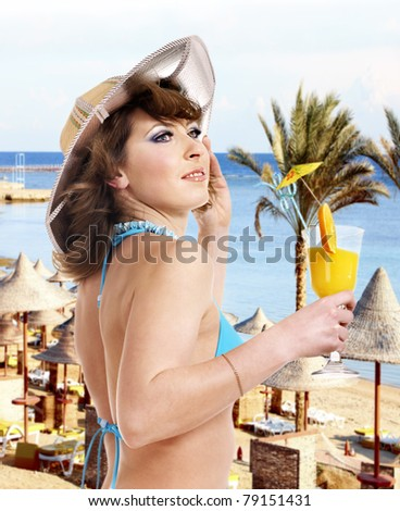 Girl in bikini on beach drinking cocktail. - stock photo