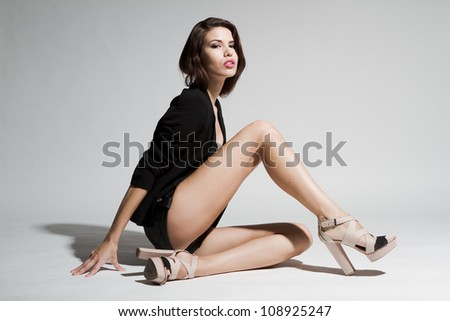 Girl in black blazer and leather shorts sitting on white background - stock photo