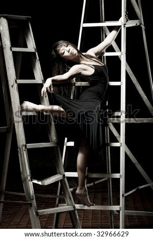 girl in black dancing on a ladder - stock photo