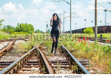 Girl in black dress walking down rail tracks - stock photo