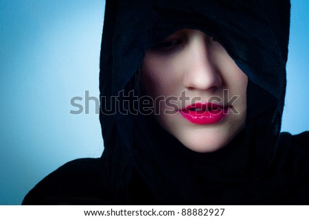 Girl in black hood against blue background - stock photo