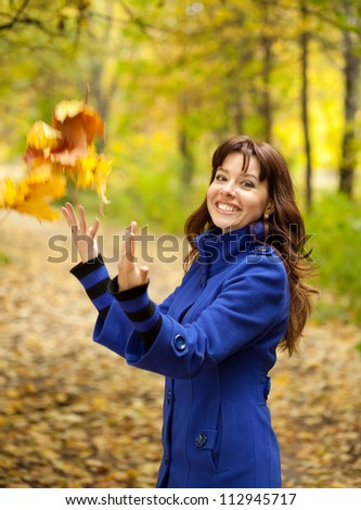 Girl in blue coat throw up maple leaves - stock photo