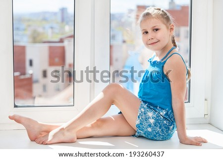 Girl in blue dress sitting on window sill in sun light - stock photo