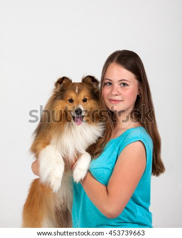 Girl in blue shirt hugging Shetland Sheepdog on a white background - stock photo