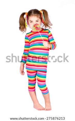 Girl in bright striped dress is holding candy on stick near the face - stock photo