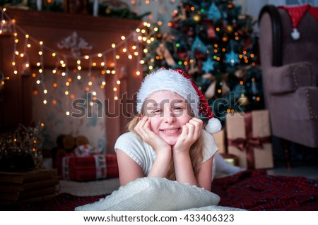 girl in Christmas cap lies on the background of fireplace and Christmas tree bright - stock photo