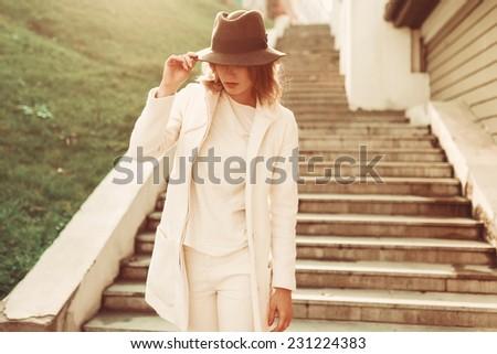 Girl in coat in the sun Posing - stock photo