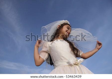 Girl in Communion dress against blue sky - stock photo