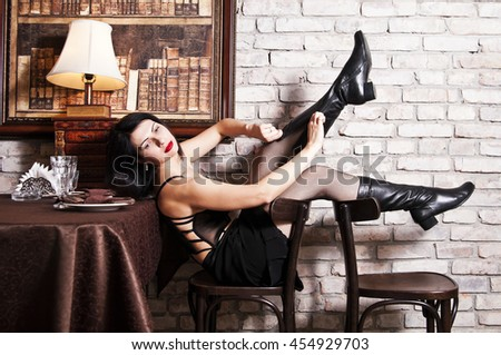 Girl in corset removes boots - stock photo