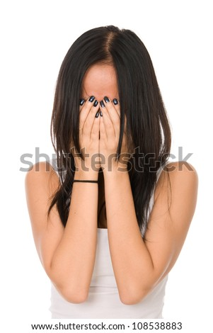 Girl in despair shuts face with hands.Isolated on white background - stock photo