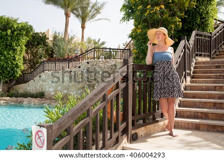 Girl in dress and hat standing on the ladder and leans on the railing - stock photo