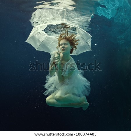 Girl in dress under water with an umbrella. - stock photo