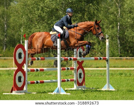 Girl in equestrian uniform on horseback jumping oxer  - stock photo