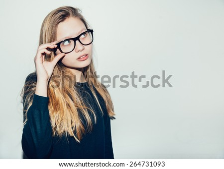 Girl in glasses looking at the top. Young beautiful woman I think it's a new idea, bingo. Smart model holds glasses. toning . Toned - stock photo