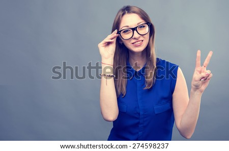 Girl in glasses show victory sign. Young beautiful modern woman. Various women's emotions. Portrait of attractive cheerful young woman in glasses pointing at space over gray background, toned.  - stock photo