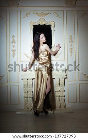 Girl in golden elegant dress over classic background - stock photo