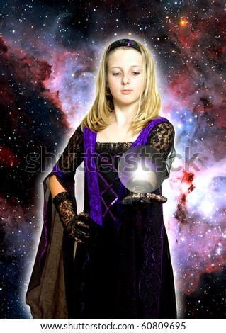 girl in gothic dress holding a sphere with light on her open hand - stock photo