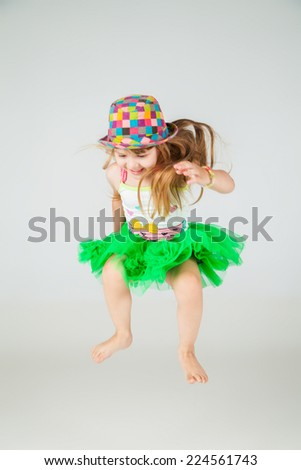 girl in green dress and hat jumps on white background - stock photo