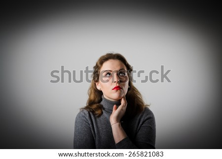 Girl in grey is full of doubts and hesitation. Girl solving a problem. - stock photo