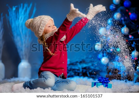 girl in hat and mittens throws snow. Christmas tree in the background - stock photo