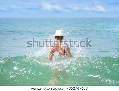 Girl in hat from the back in a spray of sea water - stock photo