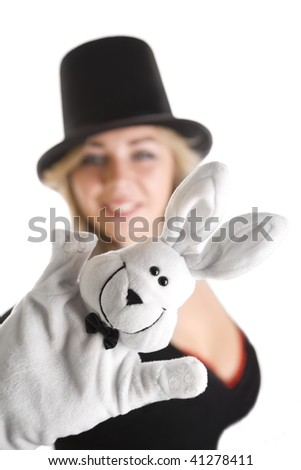 Girl in hat, with rabbit puppet on her hand. Focus on rabbit. - stock photo