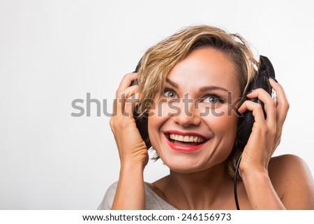 Girl in headphones. Blonde listening to music on stereo headphones. Emotions while listening to music. - stock photo