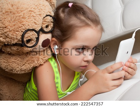 Girl in headphones with a Teddy bear lying down looking at mobile phone - stock photo