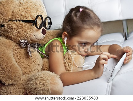 Girl in headphones with a toy bear looking at mobile phone - stock photo