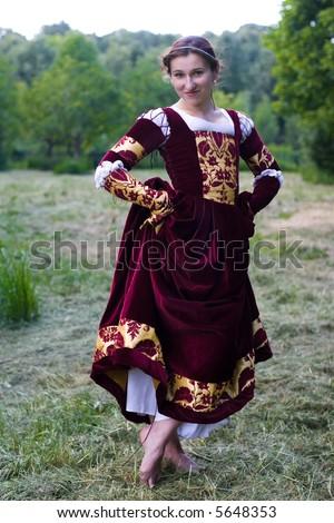 Girl in Italian renaissance dress in park - stock photo
