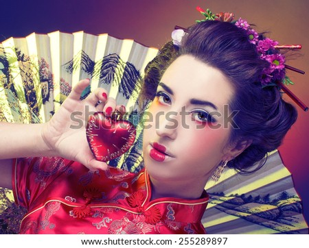 Girl in japanese style. Woman in silk red dress near big fan - stock photo