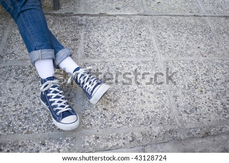 Girl in jeans and blue sneakers. - stock photo