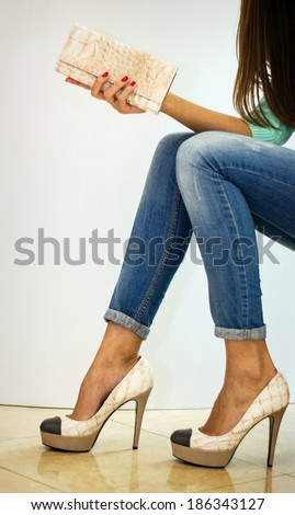 Girl in jeans and shoes with clutch. Shallow depth of field. - stock photo