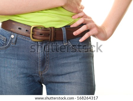 Girl in jeans with leather belt closeup - stock photo