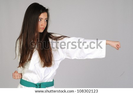 girl in Karate moves on grey background - stock photo