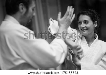 Girl in kimono showing protection technique - stock photo