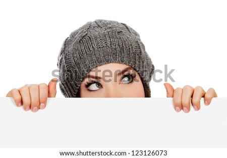 Girl in knitted hat looking over white board, white background - stock photo
