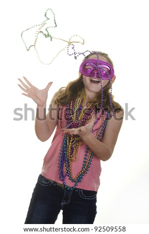 Girl in mask catching mardi gras beads - stock photo